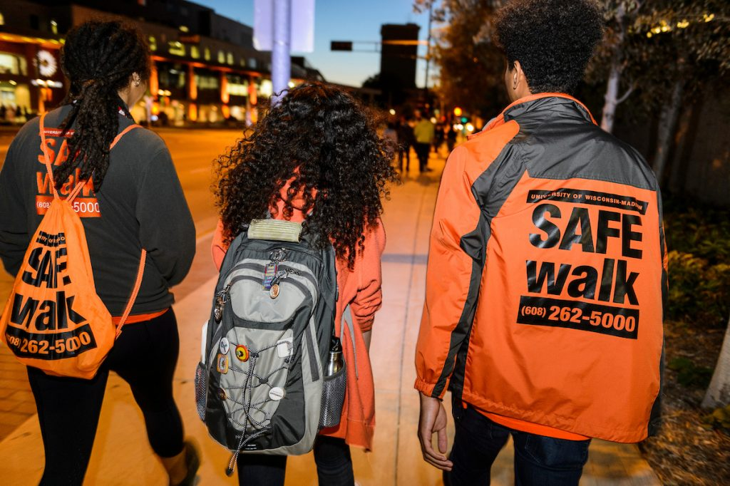three students walk away from photographer on the sidewalk at dusk
